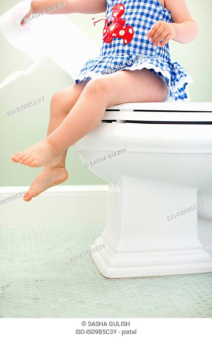 Neck down view of female toddler sitting on toilet seat pulling toilet paper
