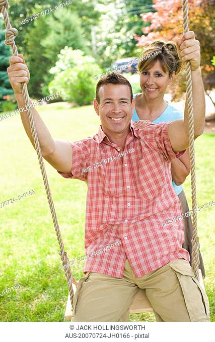 Portrait of a mature woman pushing a mature man on a rope swing and smiling