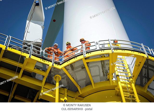 Portrait of engineers on wind turbine on offshore wind farm