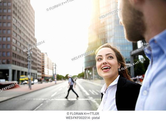Young businesswoman talking to businessman outdoors