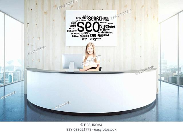 Cheerful woman sitting at reception desk with search engine optimization poster and panoramic windows with city view