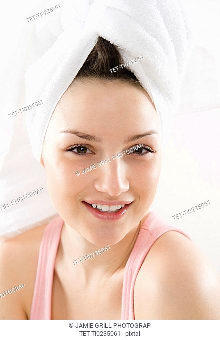 Studio portrait of smiling young woman with towel turban