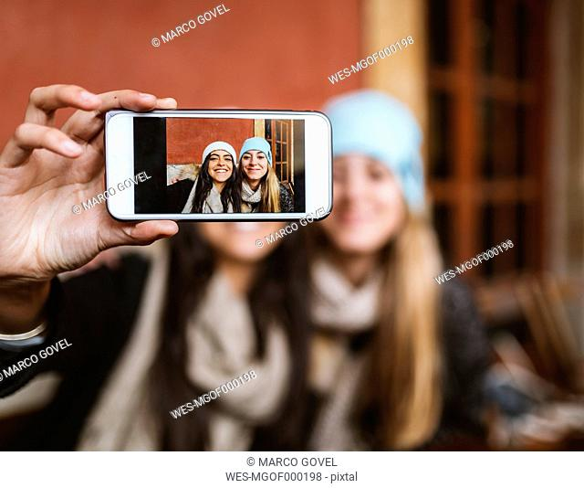 Selfie of two female friends on display of smartphone