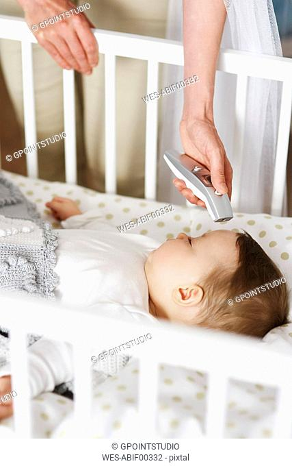 Mother with digital thermometer checking temperature of baby in crib