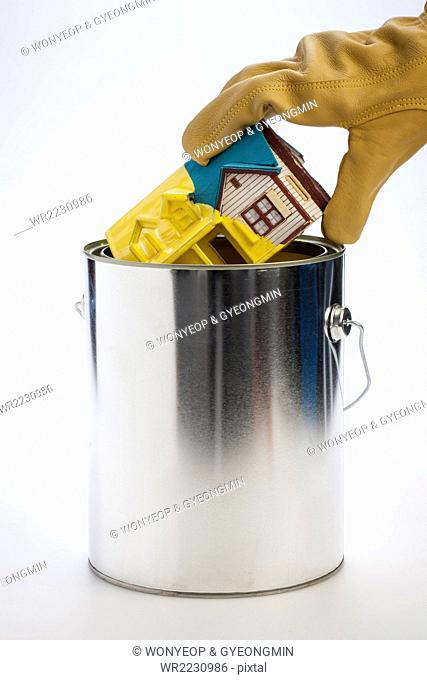 Hand in glove holding a miniature house dripping with yellow paint and taking out from a paint pot