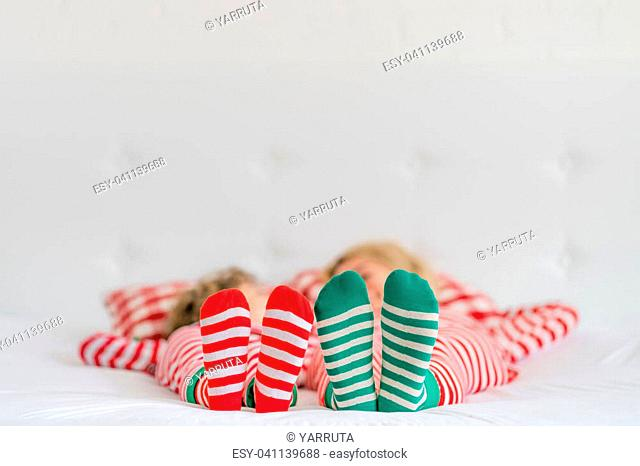 Happy family lying on bed. Mother and child having fun in Christmas time. Woman and kid relaxing at home. Winter holiday Xmas and New Year concept