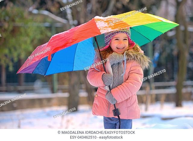 Little girl under umbrella in snowy winter