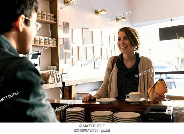 Waiter serving coffee to female customer in cafe
