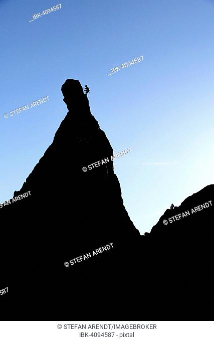 Climber on a cliff in the evening light at Savoy Alps, backlit, Chamonix, France