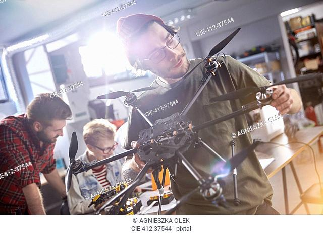 Male designer assembling drone in workshop