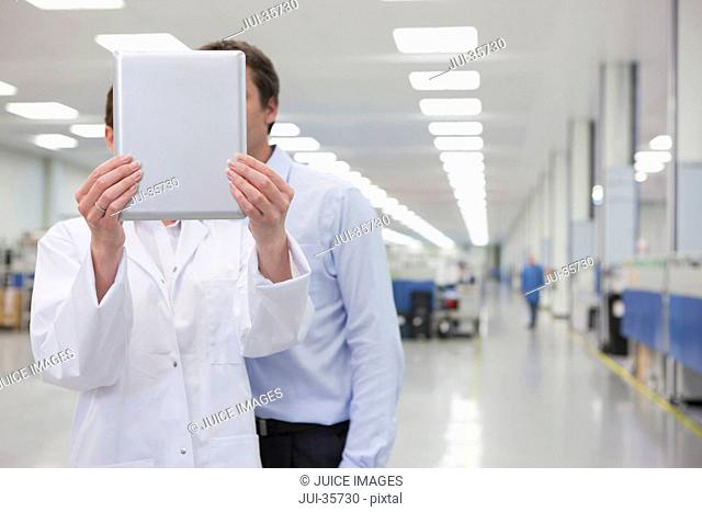 Scientist and businessman holding digital tablet in hi-tech manufacturing plant