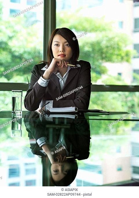 business woman sitting at table, thinking