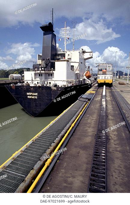 Cargo ship being guided by a mula (electric locomotive) in the Miraflores lock, Panama canal, Panama
