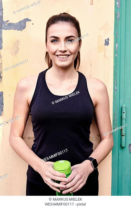 Smiling sportive woman with water bottle