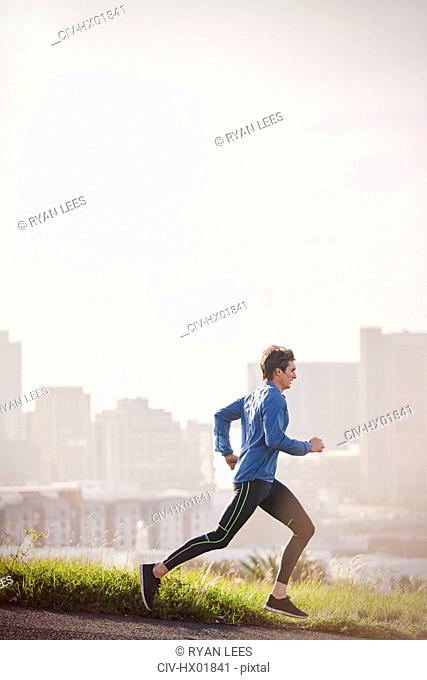 Male runner running on sunny urban city street