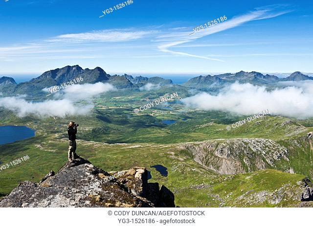Photographer takes photos of scenic mountain landscape from summit of Justadtind, Vestvagoy, Lofoten islands, Norway