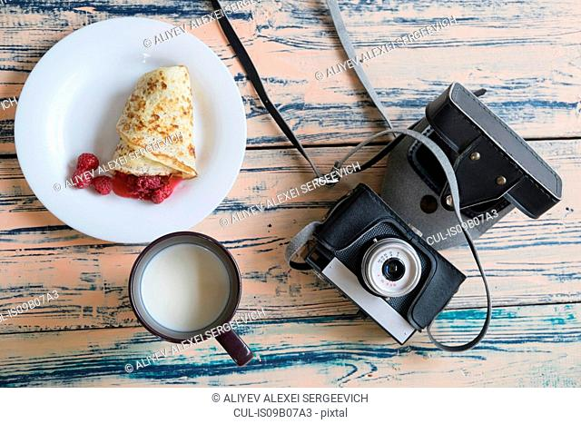 Still life of camera, pancake dessert and cup of milk, overhead view