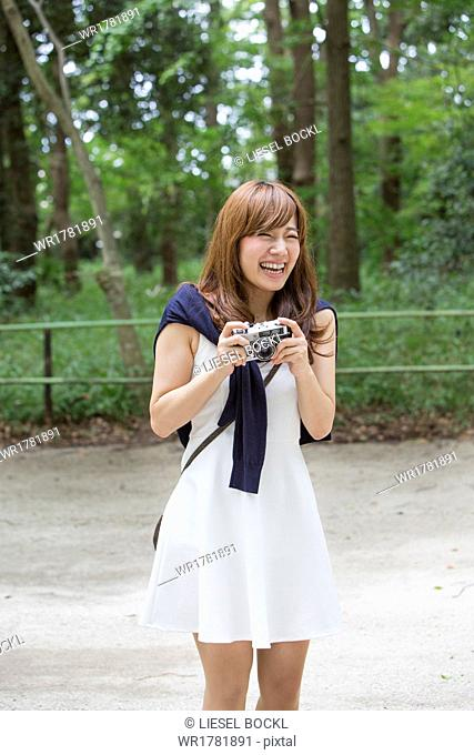 A woman in a Kyoto park holding a camera, preparing to take pictures