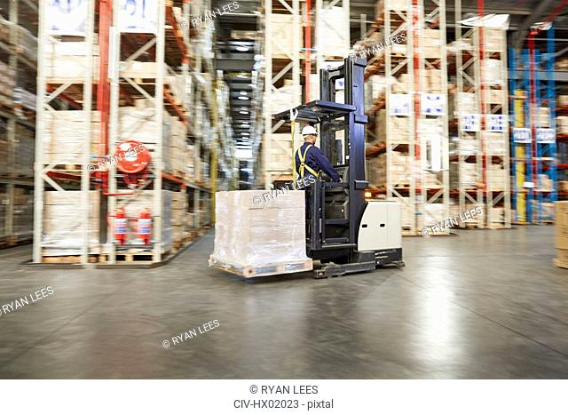 Worker operating forklift moving pallet of boxes in distribution warehouse