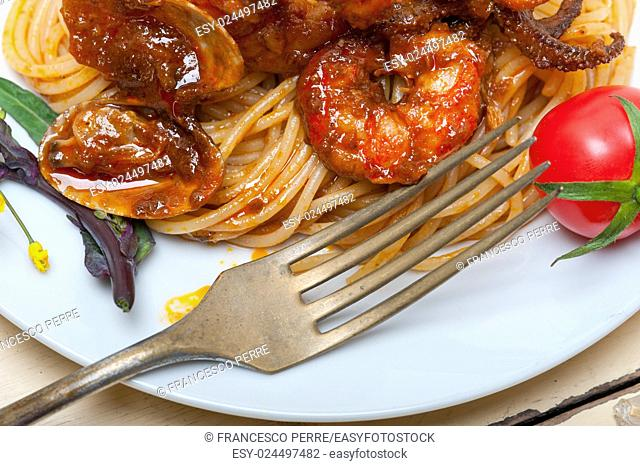 Italian seafood spaghetti pasta on red tomato sauce over white rustic wood table