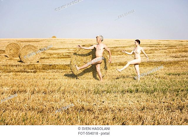 A naked man and woman marching through a field