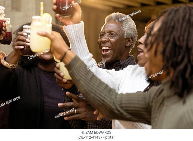 Happy, enthusiastic multi-generation family toasting lemonade and sangria