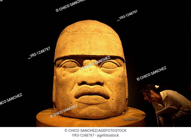 A student looks at a giant stone head as she visits the National Museum of Anthropology in Mexico City. The National Museum of Anthropology and History museum...