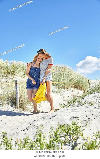 Two happy female friends walking in dunes at the beach