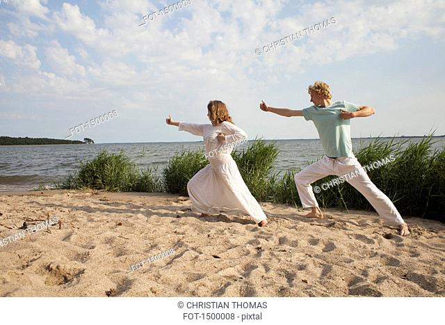 Friends practicing yoga on sea shore at beach against sky