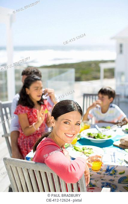 Family eating lunch at table on sunny patio overlooking ocean