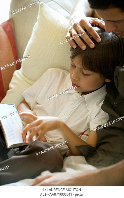 Boy reading book with his father