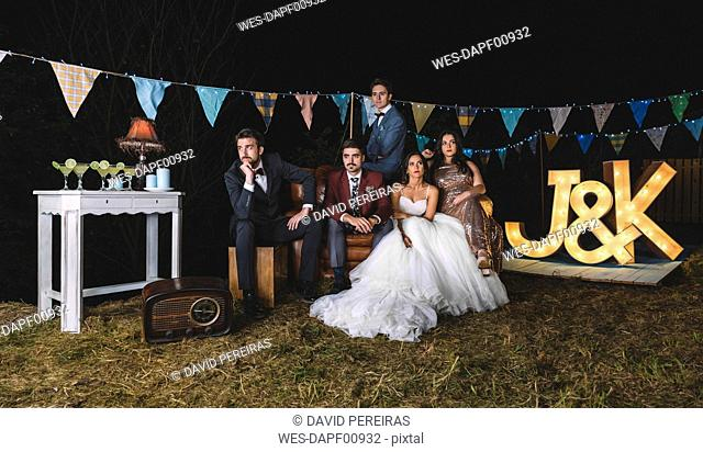 Portrait of wedding couple with friends on sofa on a night field party