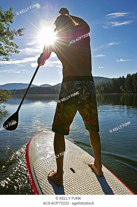 A paddle boarder enjoys a gorgeous day while on Heffley Lake, North of Kamloops in the Thompson Okanagan region of British Columbia, Canada