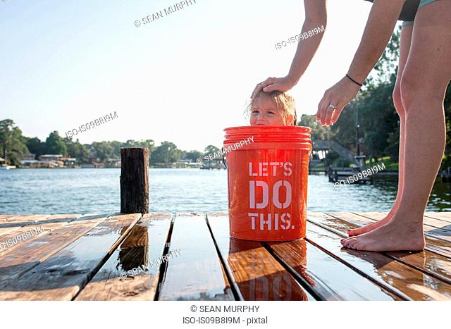 Young girl hiding in bucket on jetty