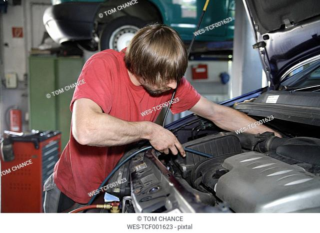 Germany, Ebenhausen, Mechatronic technician working in car garage