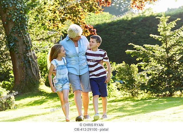 Grandmother and grandchildren walking in sunny garden