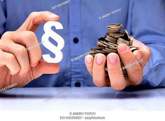 Close-up Of A Person's Hand Holding White Paragraph Symbol And Coins