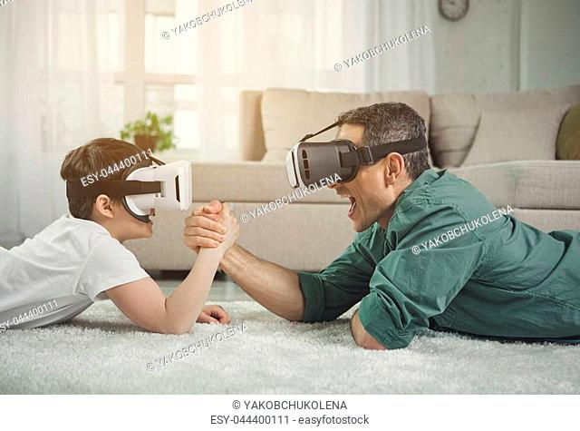 Strong man and boy competing in arm wrestling while wearing virtual reality goggles. They are situating on rug and laughing