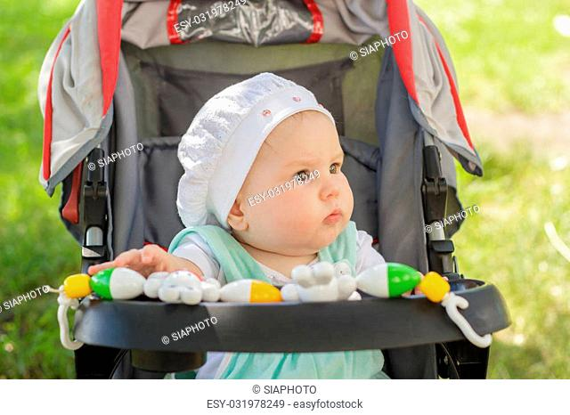 little girl sitting in a baby carriage on the street in summer
