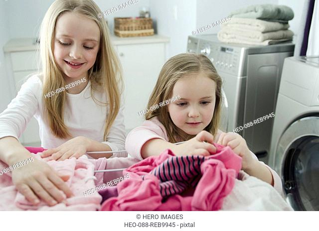 young sisters helping with laundry chores