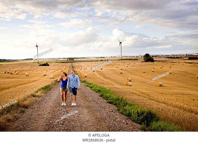 Full length of couple walking on dirt road by field against sky