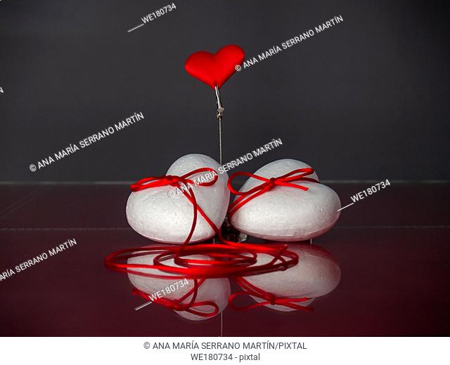 Concept of love Two poliespan hearts joined with a red thread that symbolizes the legend of the red thread and one red heart