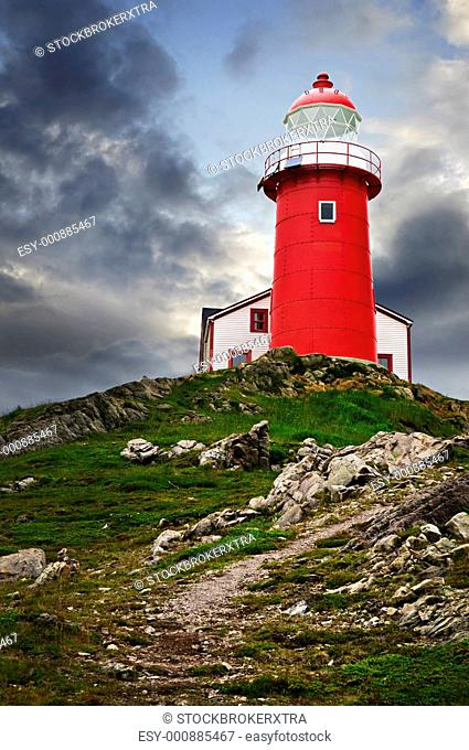 Red lighthouse on hill against stormy sky in Ferryland Newfoundland
