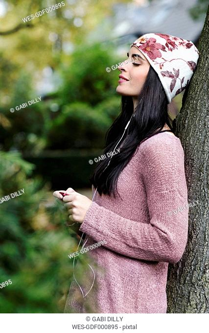 Portrait of young woman leaning against tree trunk hearing music with earphones