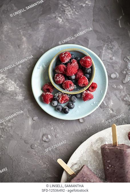 Frozen berries on a plate and in a small bowl (top view)