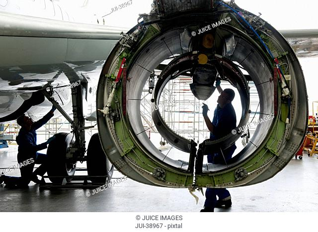 Engineer inspecting engine casing of passenger jet in hangar