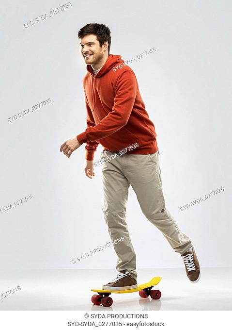 smiling young man in hoodie riding on skateboard