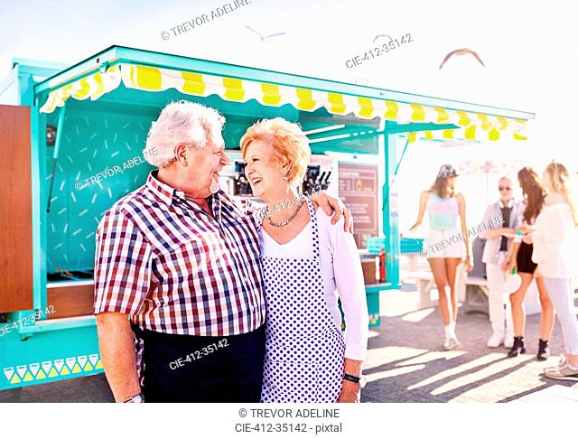 Smiling affectionate senior couple business owners outside sunny food cart