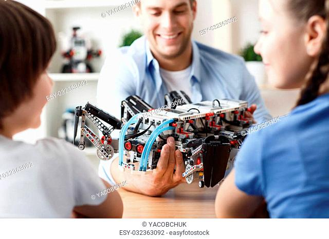Pretty toy. Cheerful pleasant father holding toy and giving it to his children while playing together