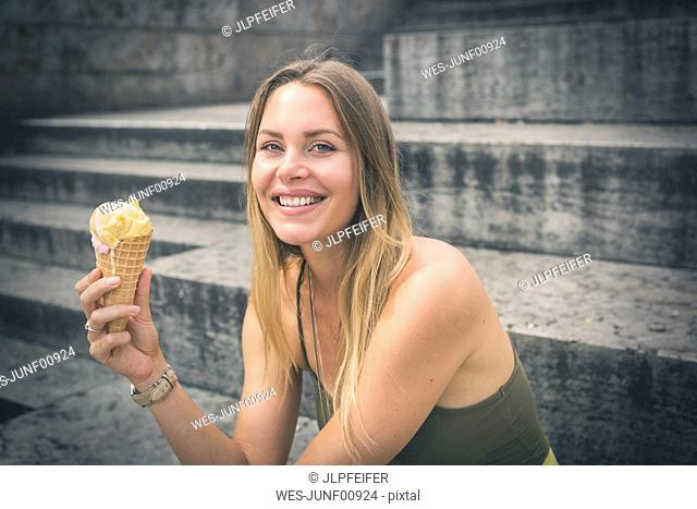 Portrait of happy young woman holding ice cream cone